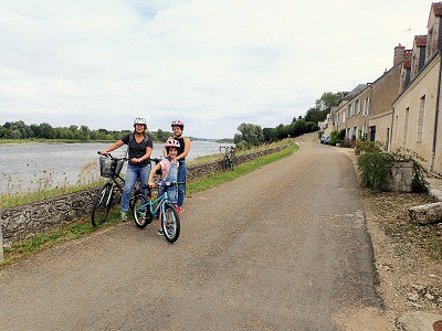 Family with bikes stood by a river