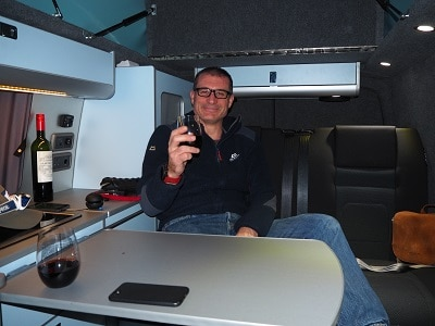 Warming up inside the van with a glass of wine