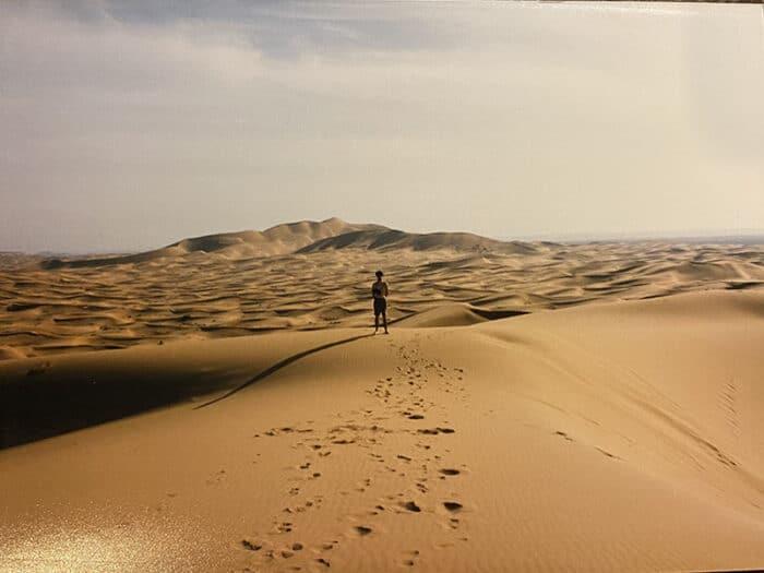Person standing on dunes in Sahara Desert