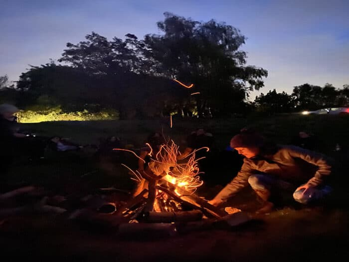 A person tending the fire at night