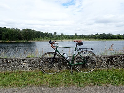A bike parked next to a river with a great view