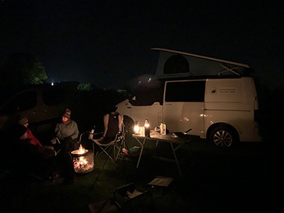 Campervan parked next to a fire at night