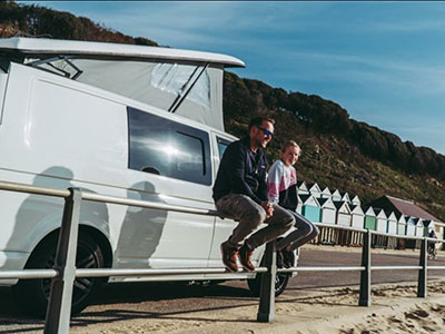 White campervan parked on the side of Bournemouth beach looking over the beach
